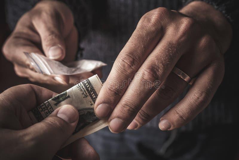 Hand van de verslaafdenmens met geld het kopen dosis cocaïne of heldin of een andere verdovend van drugdealer Druggebruik en verk stock foto
