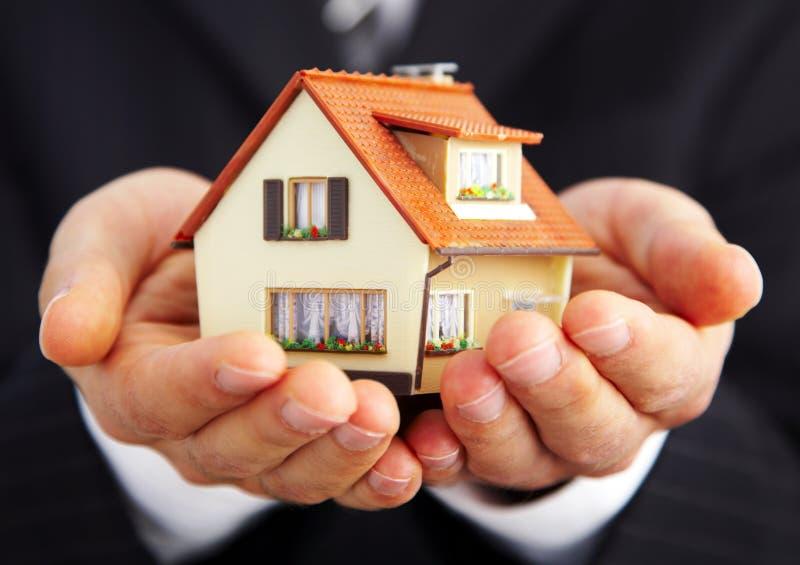 Hand van de zakenman met het huis