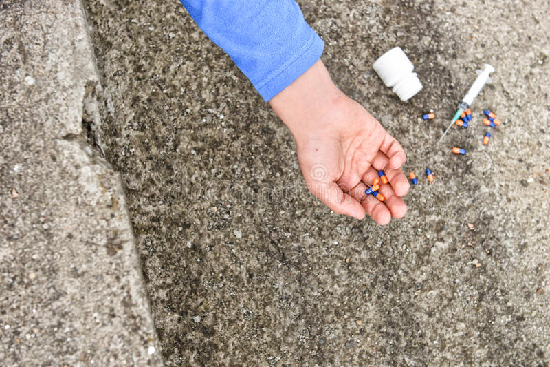 Hand van drugverslaafde dichtbij een spuit en pillen Simuleer een suici stock foto's