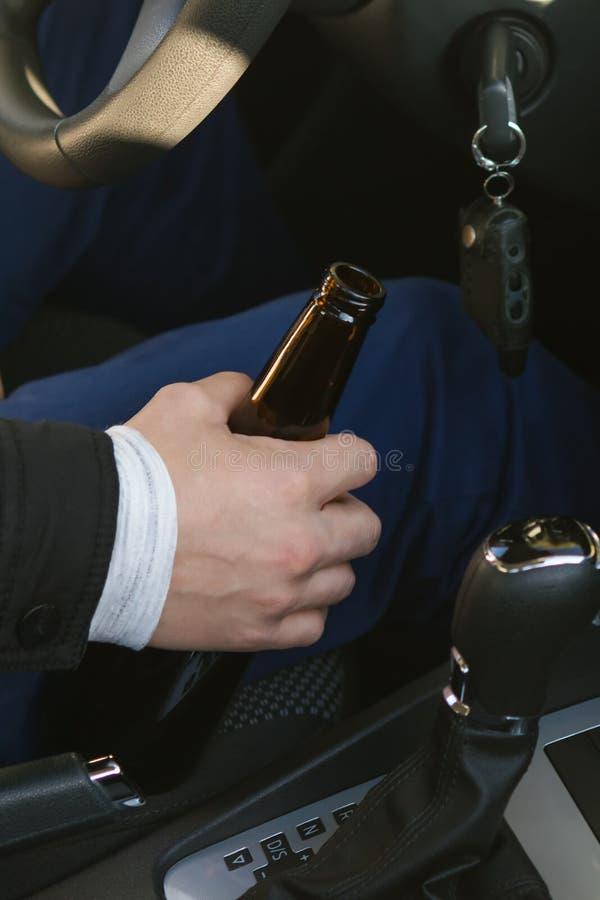 Hand van een autobestuurder die een fles alcohol bij het wiel, close-up houden stock afbeelding