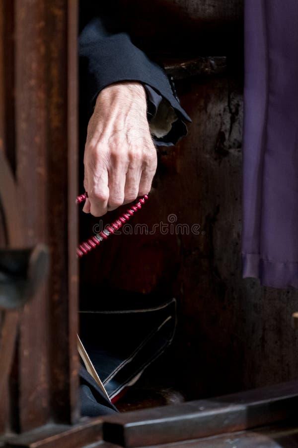 Hand van een bejaarde priesterzitting in een bekentenisdoos in een Katholieke kerk in Italië De priester houdt rozentuinparels stock afbeelding