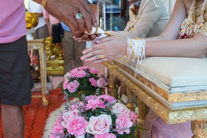 Hand van een bruid die wijwater van oudsten ontvangen stock foto