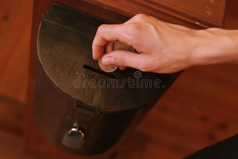 Hand van een jonge vrouw die muntstukken werpen in een schenkingsdoos Schenkingsconcept stock afbeelding