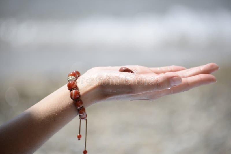 Hand van een meisje die een overzeese steen houden stock foto's