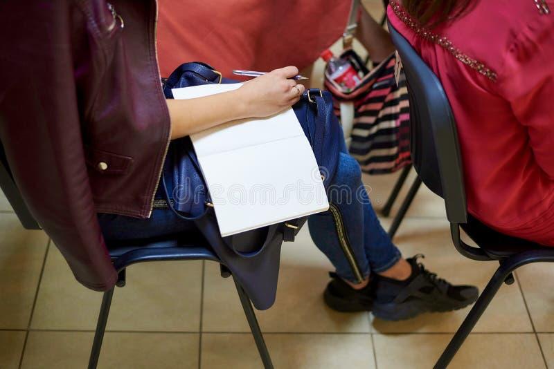 Hand van een meisje met een pen op een lege blocnote stock afbeeldingen