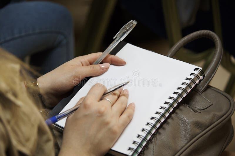 Hand van een meisje met een pen op een lege witte blocnote royalty-vrije stock fotografie