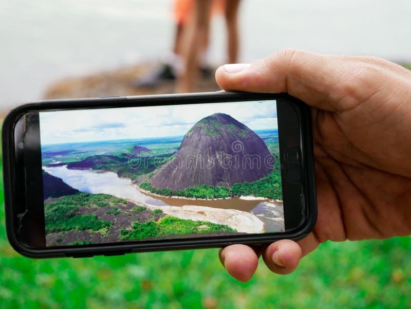 Hand van een mens die een landschapsfoto van de guainiarivier tonen die met een smartphone wordt genomen stock fotografie