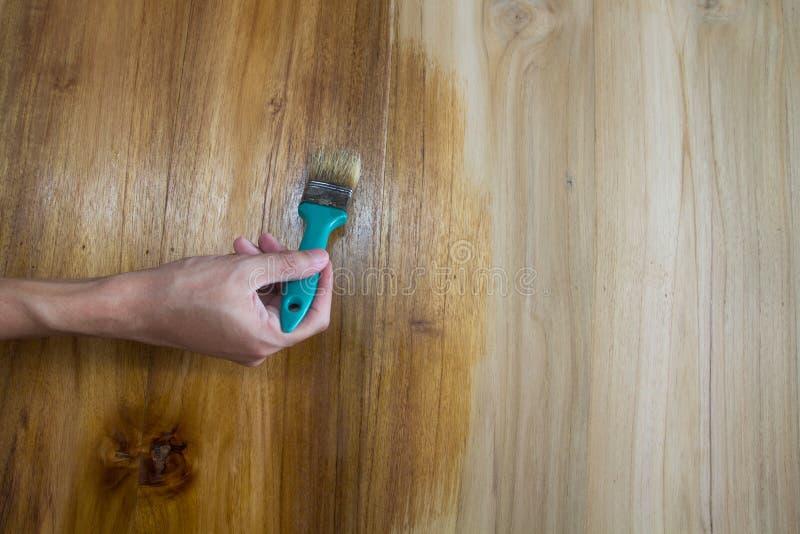 Hand van een mensenverf op houten meubilair royalty-vrije stock afbeeldingen