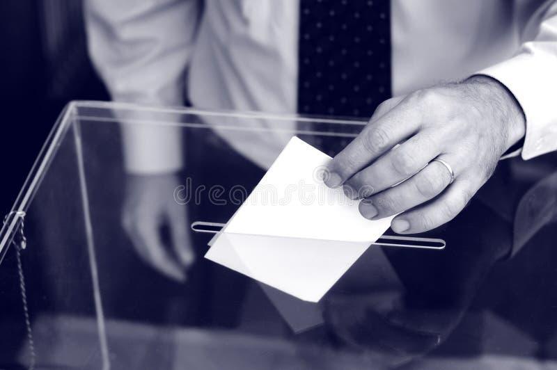 Hand van een persoon die een stemming zetten in het stemmen van over doos royalty-vrije stock fotografie