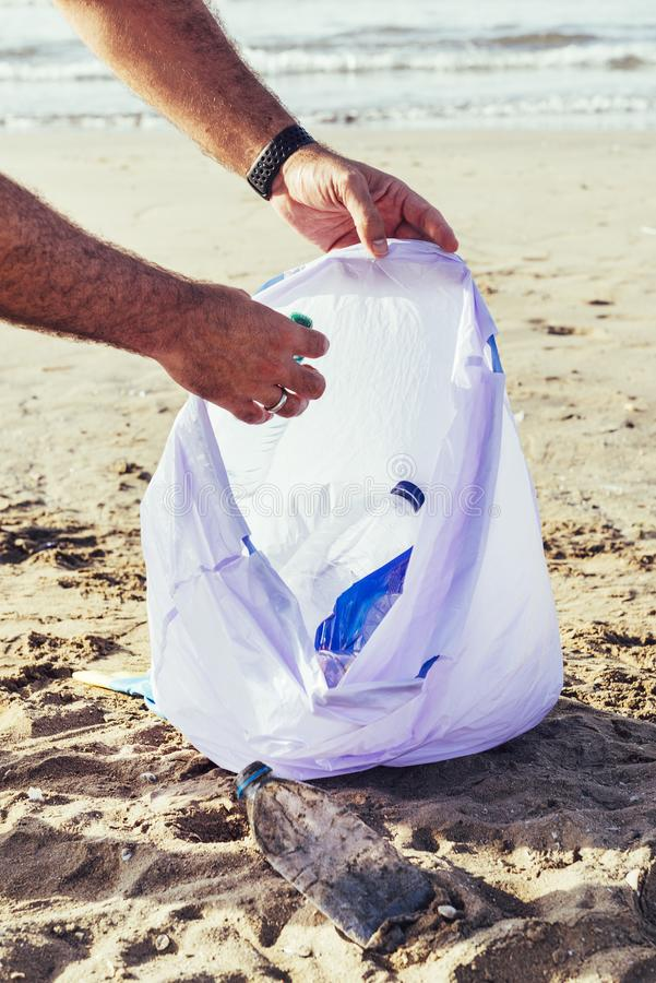 Hand van een vrijwilliger die plastieken opnemen bij strand royalty-vrije stock fotografie