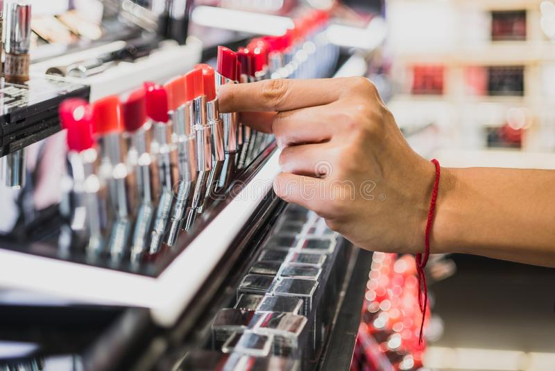 Hand van een vrouw die een rode lippenstift houden royalty-vrije stock afbeeldingen