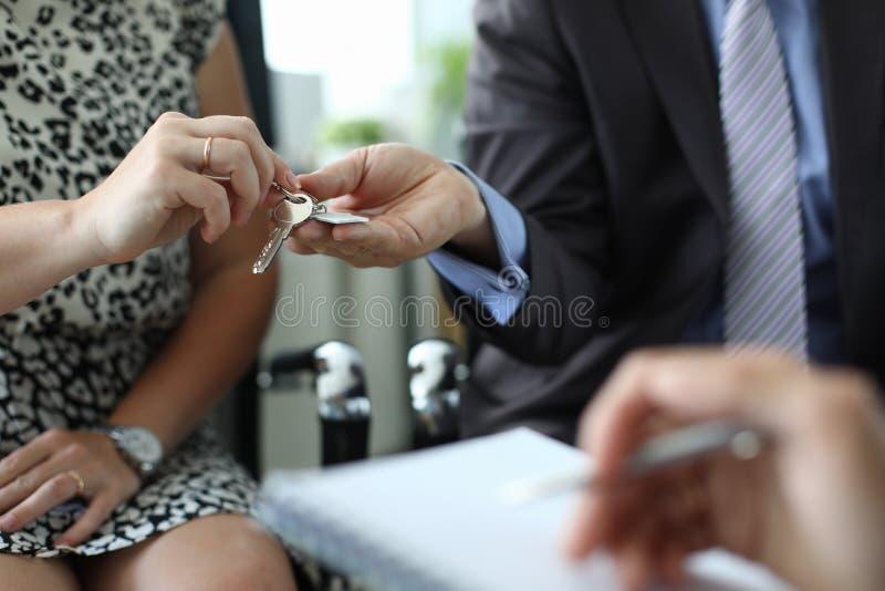 Hand van het huissleutel van de makelaar in onroerend goedgreep tegen bureau royalty-vrije stock foto's