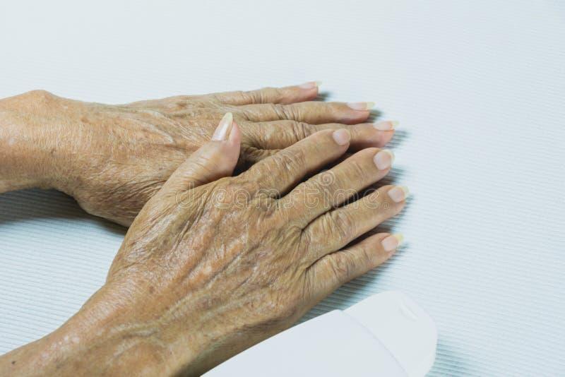 Hand van hogere vrouw met lotionfles op witte lijst royalty-vrije stock foto