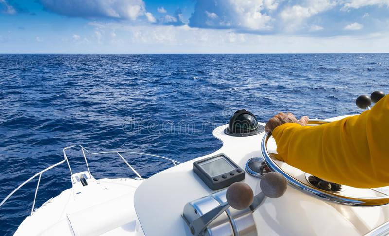 Hand van kapitein op stuurwiel van motorboot in de blauwe oceaan tijdens de visserijdag Succes visserijconcept Oceaanjacht stock fotografie