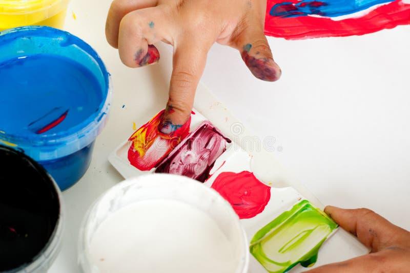 Hand van kind het schilderen met vingers stock afbeelding