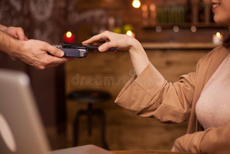 Hand van klant het betalen met mobiele telefoontechnologie zonder contact in een koffiewinkel royalty-vrije stock foto's