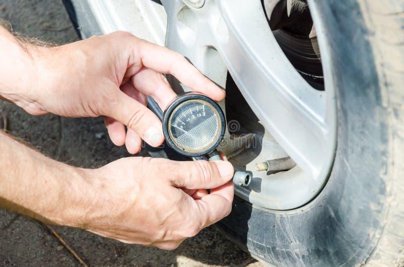 Hand van mechanische het controleren luchtdruk in band met maatclose-up stock afbeelding