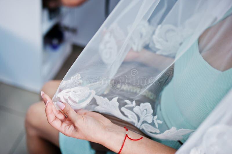 Hand van modelbruid op schoonheidssalon wat een sluier houden stock afbeelding