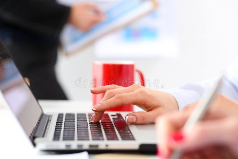 Hand van onderneemsterdrukknop bij laptop computer stock afbeelding