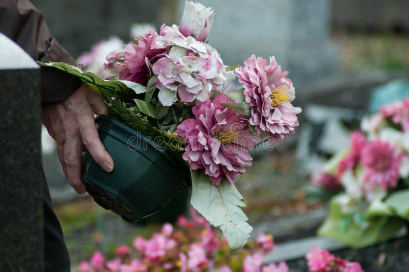 Hand van oude vrouw met kunstbloemen bij begraafplaats stock foto's