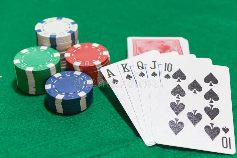 Hand van pook, Koninklijke vloed van spades, spaanders op groene achtergrond stock foto