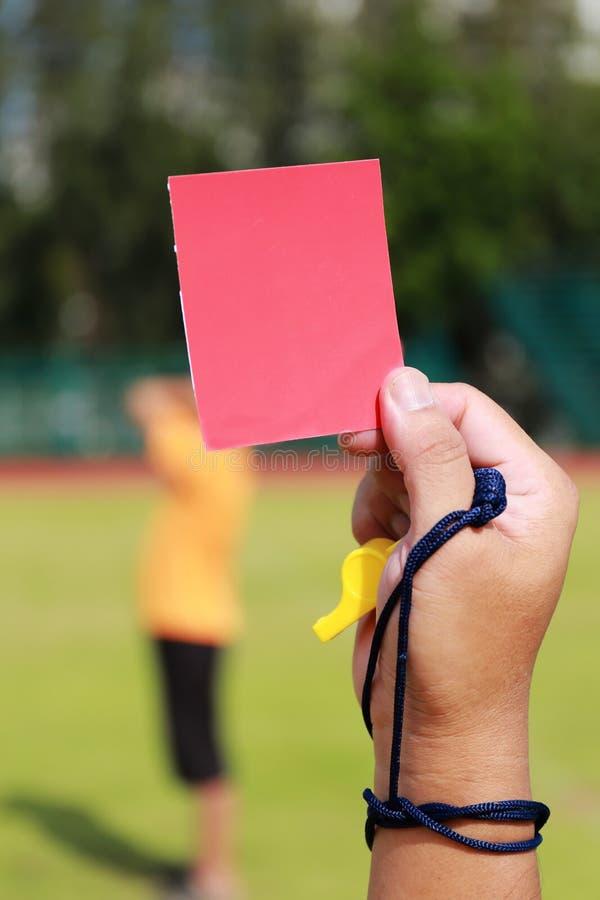 Hand van scheidsrechter met rode kaart en fluitje royalty-vrije stock afbeeldingen