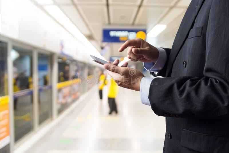 Hand van Smart device of Smartphone van de Zakenmangreep de Draadloze Digitale terwijl het wachten op Metro stock fotografie