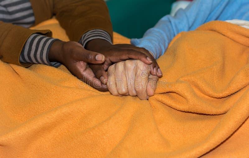Hand van verpleegster die een hogere vrouw houden Concept het helpen van handen, zorg voor de bejaarden stock afbeelding