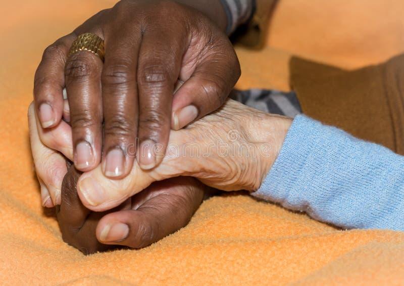 Hand van verpleegster die een hogere vrouw houden Concept het helpen van handen, zorg voor de bejaarden royalty-vrije stock afbeelding