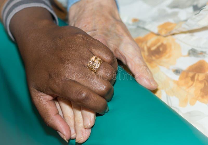 Hand van verpleegster die een hogere vrouw houden Concept het helpen van handen, zorg voor de bejaarden stock afbeeldingen