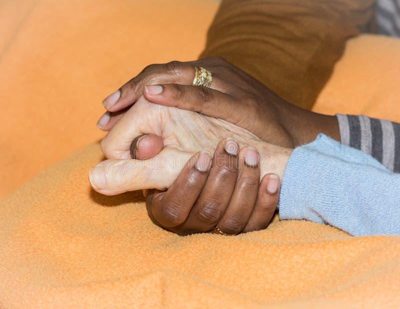 Hand van verpleegster die een hogere vrouw houden Concept het helpen van handen, zorg voor de bejaarden stock fotografie