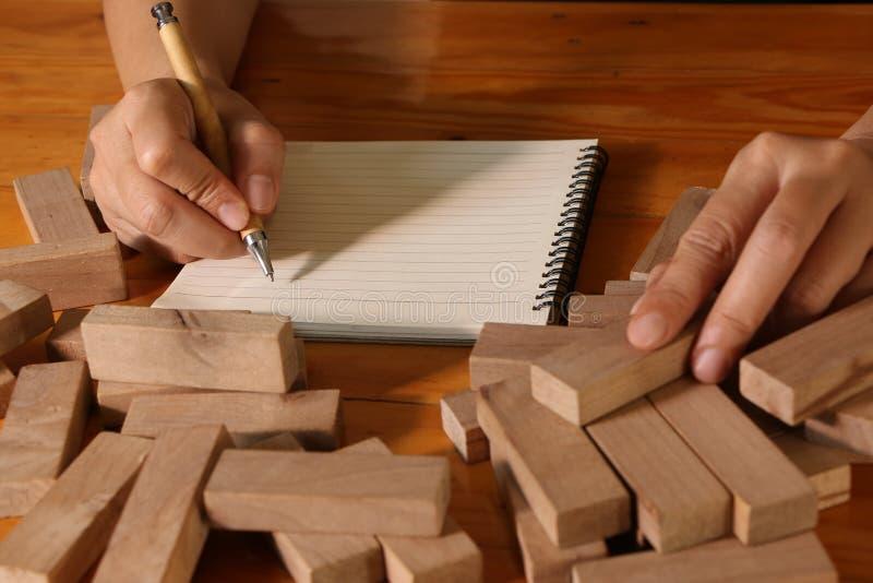 Hand van vrouw het schrijven op notaboek en het houden van houten blok, risico en strategie in zaken royalty-vrije stock fotografie