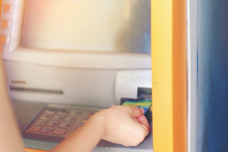 Hand van vrouwen met een creditcard, die ATM gebruiken Sluit omhoog ATM F royalty-vrije stock afbeelding