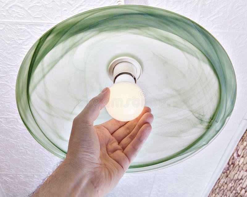 Hand verdreht energiesparende LED-Lampe auf Deckenleuchte stockfoto