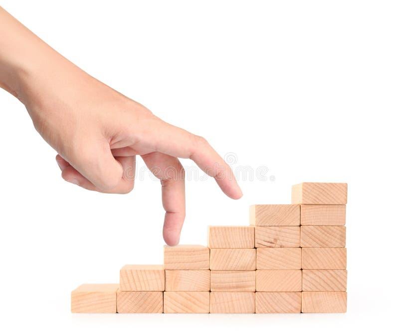 Hand vergleichen die Geschäftsperson, die Spielzeugtreppenhaus steigert stockbild