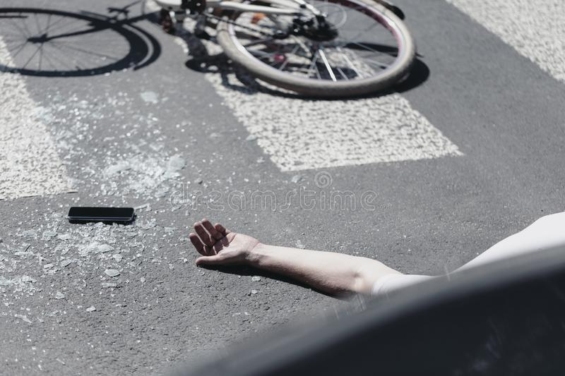 Hand of victim on pedestrian crossing next to bike after dangerous traffic accident royalty free stock photo