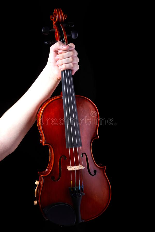 Hand with a violin on a black background, close-up. music concept. Details of the violin. Orchestra, violinist, classic, symphony, play, player, concert royalty free stock image