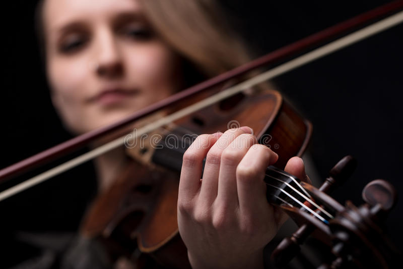 Hand of a violinist playing. Hand closeup detail over a blurred face of a young woman violinist player playing her instrument on her shoulder holding bow royalty free stock image