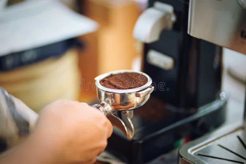 Hand von barista portafilter halten gefüllt mit dem gemahlenen Kaffee, der sich vorbereitet, mit Maschine zu brauen lizenzfreie stockfotos
