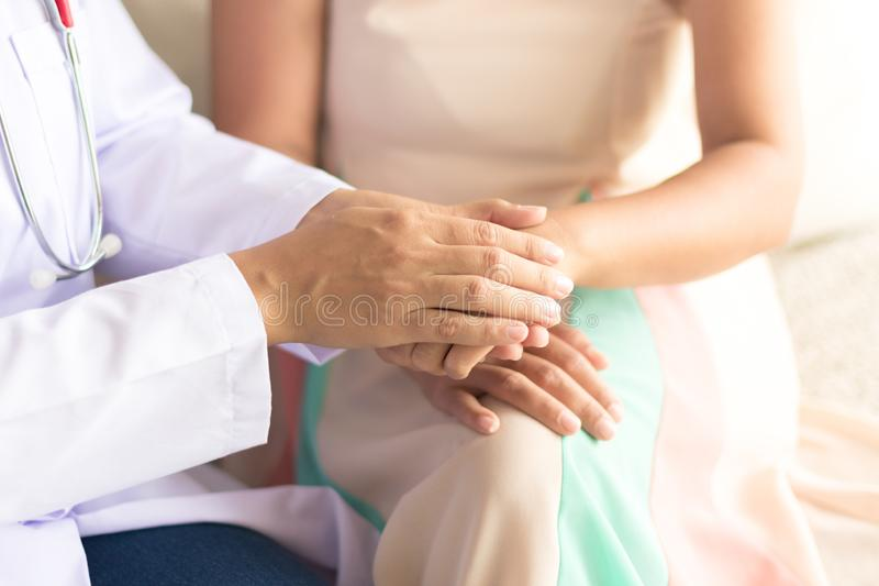 Hand von Doktor ihrem weiblichen Patienten versichernd stockfotografie