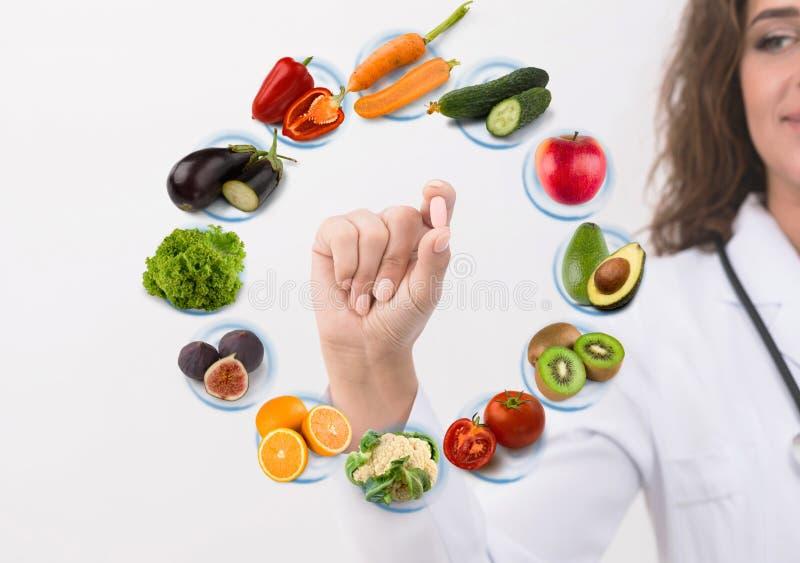 Hand von Ernährungswissenschaftlerdoktor Pille auf Symbolfrüchten zeigend stockbild
