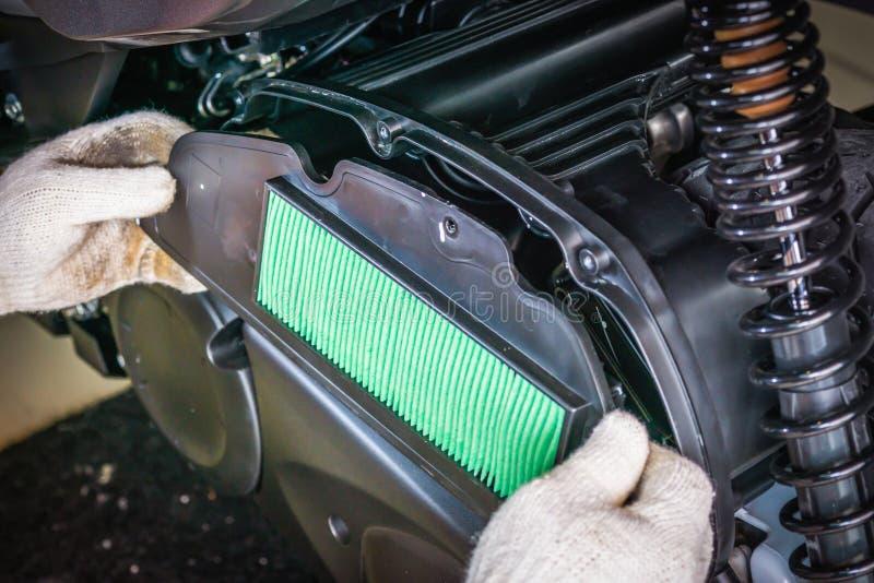 Hand von Mechaniker Install-Luftfilter auf großem Roller wartung stockfoto