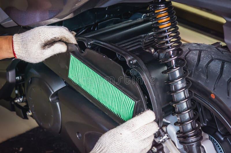 Hand von Mechaniker Install-Luftfilter auf großem Roller wartung stockbilder