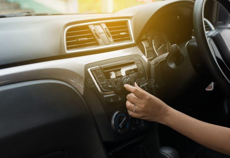 Hand vrouwelijke bestuurder wat betreft het scherm en het aanzetten van het systeem van de autoradio, Knoop op dashboard in autop royalty-vrije stock fotografie