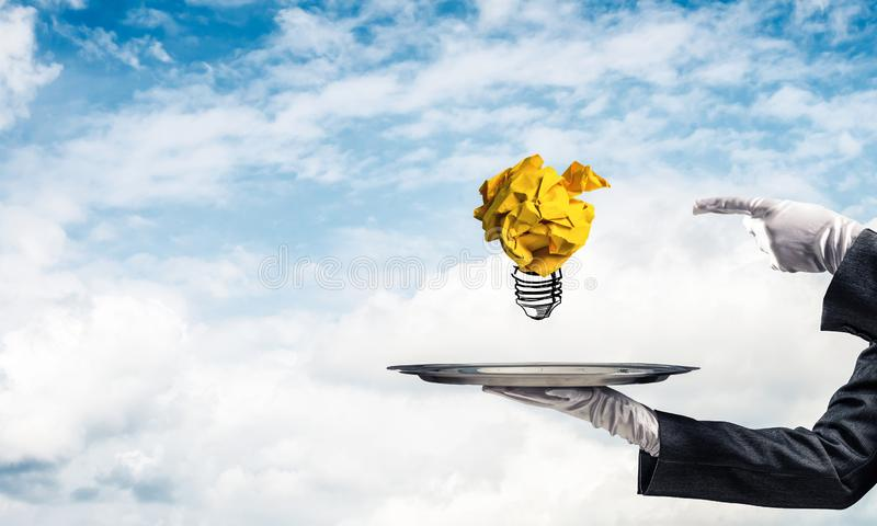 Hand of waiter presenting crampled paper lightbulb. Cropped image of waitress`s hand in white glove presenting crumpled paper lightbulb on metal tray and stock illustration