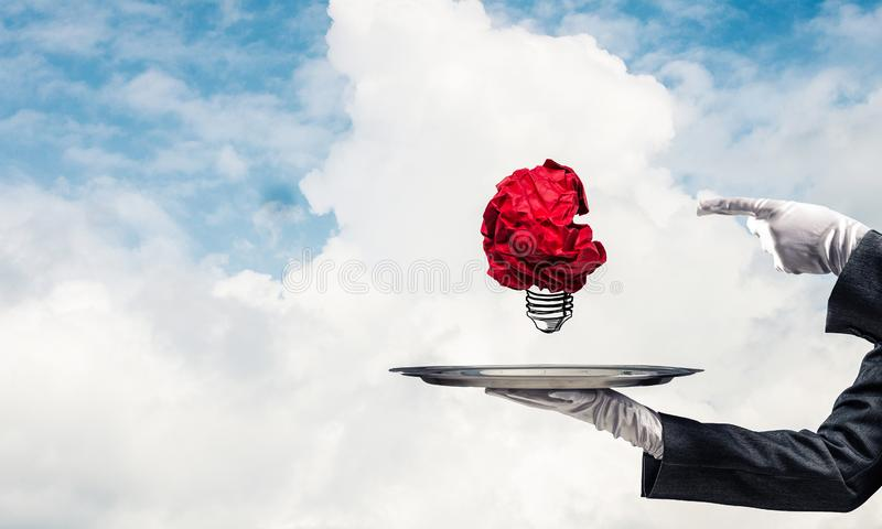 Hand of waiter presenting crampled paper lightbulb. Cropped image of waitress`s hand in white glove presenting crumpled paper lightbulb on metal tray and vector illustration
