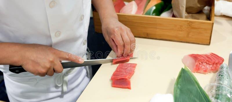Hand war der geschnittene Fisch, zum von Sushi zu machen lizenzfreie stockfotografie