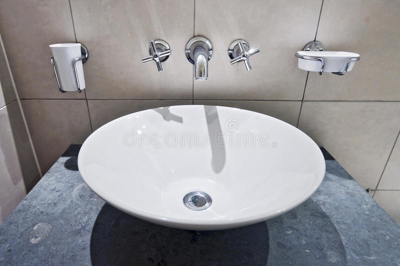 Hand wash bowl. Modern round hand wash basin with wall mount holders stock photography