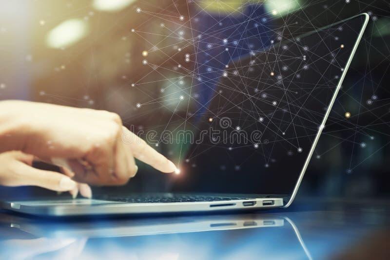 Hand wat betreft laptop met globale de technologiepictogrammen van de netwerkverbinding op het scherm Toekomstige zaken online, m stock foto