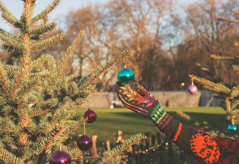 Hand wat betreft snuisterij op Kerstmisboom buiten royalty-vrije stock afbeelding
